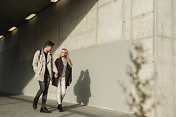Young couple holding hands and walking through underpass, Munich, Bavaria, Germany