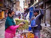 06 MARCH 2017 - KATHMANDU, NEPAL: An Indian migrant worker sells a Nepali woman fresh fruit in Kathmandu. Many of the itinerant fruit peddlers in Kathmandu are migrant workers from India.      PHOTO BY JACK KURTZ