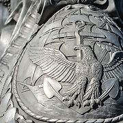An eagle shield on the base of the Navy-Merchant Marine Memorial in Arlington, Virginia, on Columbia Island on the banks of the Potomac across from Washington DC. The memorial honors those who lost their life at sea in World War I and was dedicated in 1934. The main sculpture is cast from aluminum.