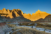 A hiker explores rock formations north of Ben Reifel Visitor Center near sunset in Badlands National Park, South Dakota, USA. The intricately carved cliff of the Badlands Wall constantly retreats as it erodes and washes into the White River Valley below.