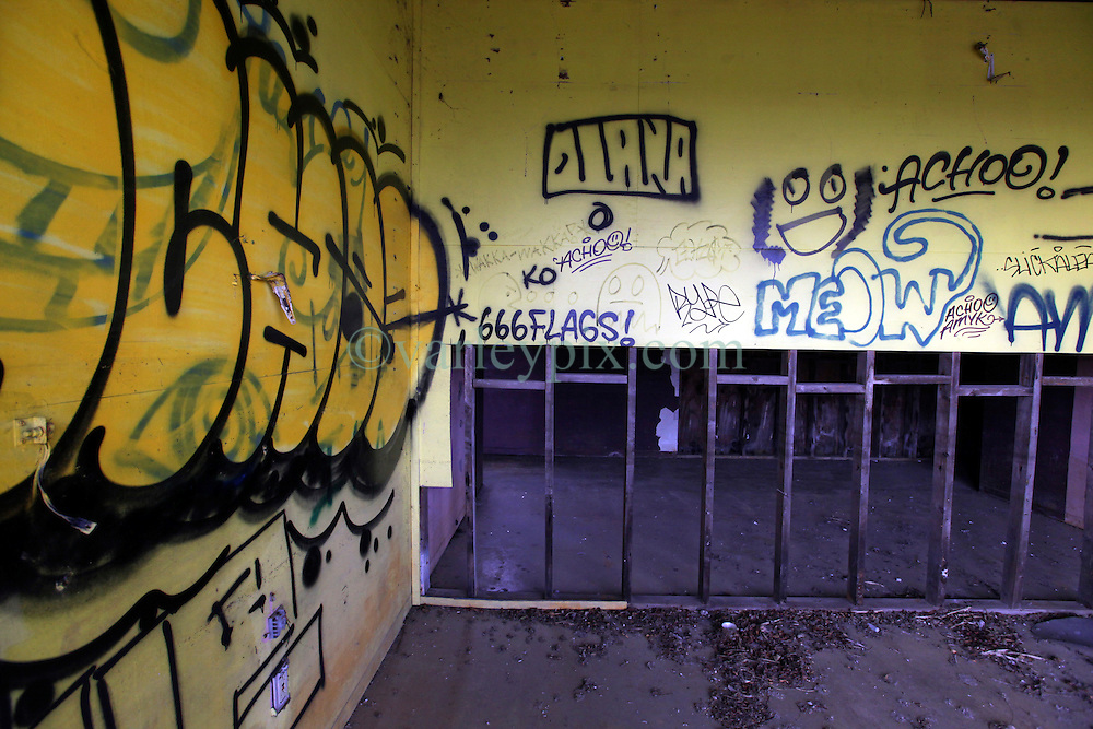 15 April 2016. New Orleans, Louisiana.<br /> Abandoned Six Flags amusement park in New Orleans East.<br /> Not amusing any more. 'Closed for storm.' Six Flags.<br /> Signs of devil worship can be found on the site. From graffiti depicting 666 and upside down crosses. A security guard confirmed he has ejected Devil worshippers from the abandoned former amusement park. The park radiates an eerie post apocalyptic sense of foreboding in it's dereliction. The park was destroyed by hurricane Katrina in August 2005, stripped by copper thieves and is slowly being reclaimed by the land it stands on. The site is now home to thriving wildlife. Would be developers for the former Jazzland site have proposed various ideas over the years to revive the area into a theme park and shopping complex, proposals which have been rejected by the Industrial Development Board. <br /> Photo; Charlie Varley/varleypix.com