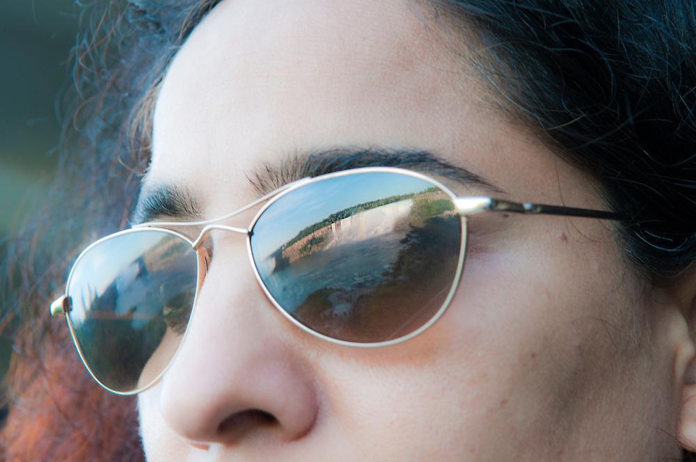 Frau nit Sonnenbrille blickt auf die Niagarafälle  entlang der amrikanisch-kanadischen Grenze.Der Abschnitt heisst Amrican Falls   |  A woman with sunglasses looks at the Niagara Falls  - the part is called  the American Falls along the american canadian frontier    |
