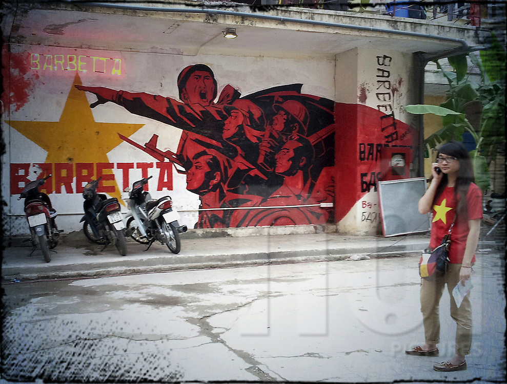 A vietnamese teenager stands in front of a propaganda style graffiti in Zone 9, Hanoi, Vietnam, Southeast Asia