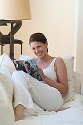 Woman enjoying reading a magzine relaxed on a white sofa