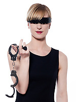 beautiful blond woman on studio white background holding handcuffs offering herself