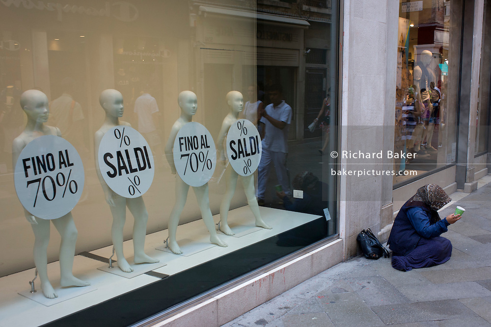 Retail mannequins advertising a 70% sale with a woman street beggar in the San Marco shopping district of Venice, Italy.