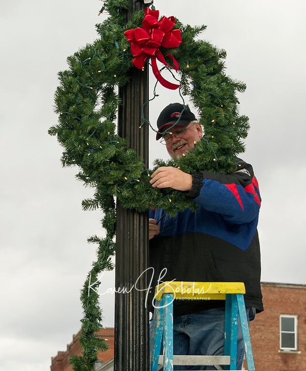 Tony Felch hangs Christmas wreaths and garland on light poles lining Main Street downtown Saturday afternoon hosted by Celebrate Laconia.  .  (Karen Bobotas/for the Laconia Daily Sun)
