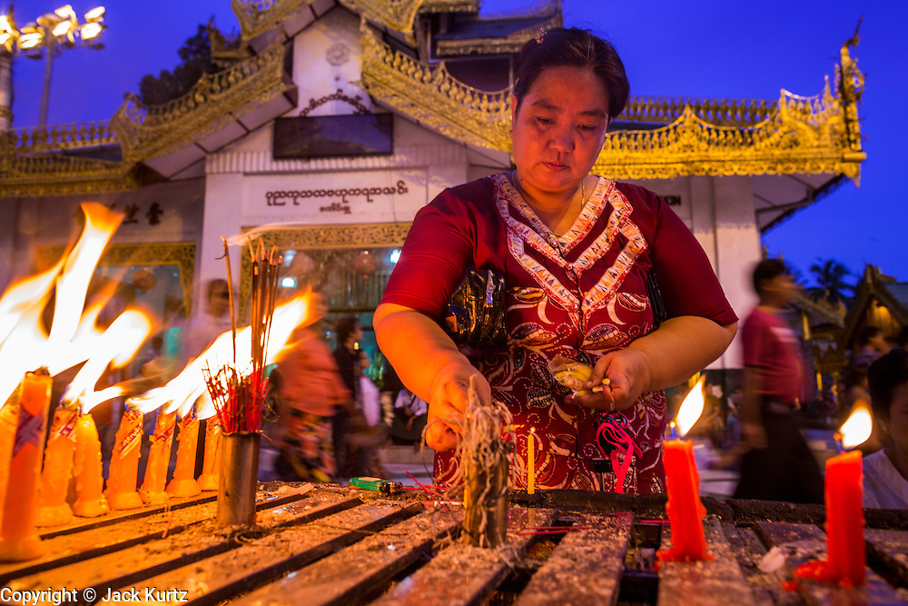 15 JUNE 2013 - YANGON, MYANMAR: A woman makes merit and prays with candles at Shwedagon Pagoda. The Shwedagon Pagoda is officially known as Shwedagon Zedi Daw and is also called the Great Dagon Pagoda or the Golden Pagoda. It is a 99 metres (325 ft) tall pagoda and stupa located in Yangon, Burma. The pagoda lies to the west of on Singuttara Hill, and dominates the skyline of the city. It is the most sacred Buddhist pagoda in Myanmar and contains relics of the past four Buddhas enshrined: the staff of Kakusandha, the water filter of Koṇāgamana, a piece of the robe of Kassapa and eight strands of hair fromGautama, the historical Buddha. The pagoda was built between the 6th and 10th centuries by the Mon people, who used to dominate the area around what is now Yangon (Rangoon). The pagoda has been renovated numerous times through the centuries. Millions of Burmese and tens of thousands of tourists visit the pagoda every year, which is the most visited site in Yangon.    PHOTO BY JACK KURTZ
