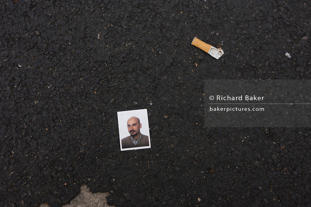 Dropped or discarded passport portrait of an Italian man lies on the ground next to a smoked cigarette butt.