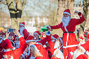 TThe warm up - hosuands of runners, of all ages, in santa suits and other Christmas costumes runaround Clapham Common for Great Ormond Street Hospital and for fun. London 30 Nov 2016