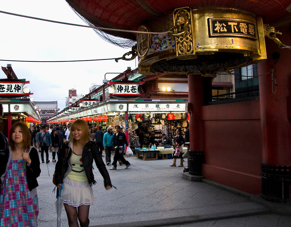 Two girls pass the giant lantern of the Kaminarimon or Thunder Gate, Asakusa, Tokyo. It's an entrance gate to the Senso-jo buddhist temple, popular with tourists and pilgrims..