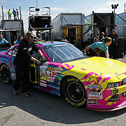The crew for Rousch-Fenway Racing Ford driver Travis Pastrana is seen pushing his car in the garage area, during a NASCAR Drive4COPD Nationwide Series practice session at Daytona International Speedway on Thursday, February 21, 2013 in Daytona Beach, Florida.  (AP Photo/Alex Menendez)
