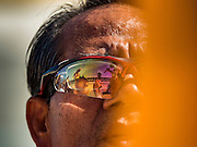"""02 JANUARY 2016 - KHLONG LUANG, PATHUM THANI, THAILAND: A woman using a smart to take pictures is reflected in the glasses of a man praying at Wat Phra Dhammakaya on the first day of the 5th annual Dhammachai Dhutanaga (a dhutanga is a """"wandering"""" and translated as pilgrimage). More than 1,300 monks are participating pilgrimage through central Thailand. The purpose of the pilgrimage is to pay homage to the Buddha, preserve Buddhist culture, welcome the new year, and """"develop virtuous Buddhist youth leaders."""" Wat Phra Dhammakaya is the largest Buddhist temple in Thailand and the center of the Dhammakaya movement, a Buddhist sect founded in the 1970s. The monks are using busses on some parts of the pilgrimage this year after complaints about traffic jams caused by the monks walking along main highways.          PHOTO BY JACK KURTZ"""