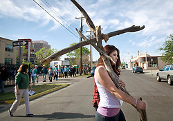 April 14, 2017 - Albuquerque, New Mexico, U.S. - ANGEL VIGIL carries a wooden cross as she helps to lead a procession from Immaculate Conception Church to Crossroads for Women, during Friday's Urban Way of the Cross pilgrimage around Downtown Albuquerque. People from various churches and organizations stopped at different locations for the nine stations to reflect on Good Friday. (Credit Image: © Albuquerque Journal via ZUMA Wire)