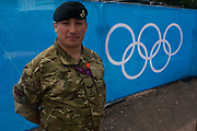 A portrait of a Lance Corporal in the Rifles regiment of the British army next to the Olympic rings logo before the start of the canoe slalom heats at the Lee Valley White Water Centre, north east London, on day 3 of the London 2012 Olympic Games. A further 1,200 military personnel are being deployed to help secure the 2012 Olympics in London following the failure by security contractor G4S to provide enough private guards. The extra personnel have been drafted in amid continuing fears that the private security contractor's handling of the £284m contract remains a risk to the Games.