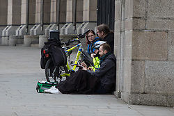 London, March 22nd 2017. Police officers appear to be taking a statement from a man seated on the ground, within the cordon, in the aftermath of a shooting incident on Westminster Bridge, where several pedestrians were also mown down by a car.