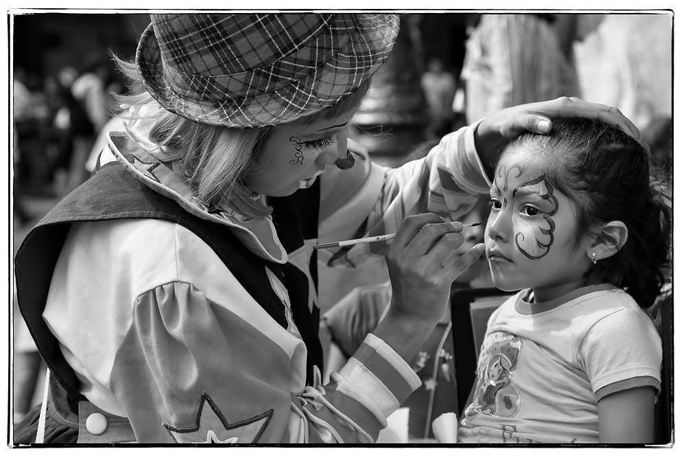 Clown making up a very cute little girl in the street of Puebla, Mexico