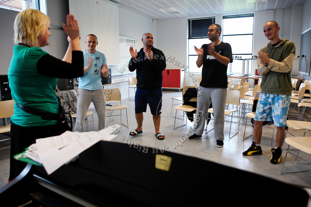 Inmates (facing camera) and their instructor are clapping hands and singing during the time they regularly spend learning and practicing music arts inside the luxurious Halden Fengsel, (prison) near Oslo, Norway.