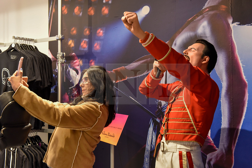 """© Licensed to London News Pictures. 18/10/2018. LONDON, UK.  A visitor takes a selfie with a waxwork of Freddie Mercury at the Queen pop-up shop which has opened in Carnaby Street.  Coinciding with the release next week of the movie """"Bohemian Rhapsody"""", the shop offers Queen music fans memorabilia, a display of stage costumes as well as archived Queen performance footage.  Photo credit: Stephen Chung/LNP"""