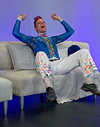 An actor in a painted-on costume howls in laughter at the position he finds himself in.