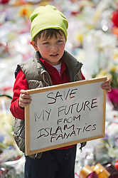© London News Pictures. 25/05/2013. Woolwich, UK. A boy (permission given to take pic but would not give name) holding a sign reading ' SAVE MY FUTURE FROM ISLAMIC FANATICS' outside Woolwich Barracks in South East London.  Drummer Lee Rigby was murdered by two men in Woolwich town centre in what is being described as a terrorist attack. Photo credit: Ben Cawthra/LNP