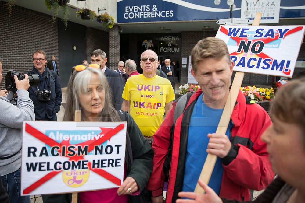 © Licensed to London News Pictures . 29/09/2017 . Torquay , UK . A protest against UKIP outside the venue is photobombed by a UKIP anti-Islam campaigner . The UK Independence Party Conference at the Riviera International Centre . UKIP is due to announce the winner of a leadership election which has the potential to split the party . Photo credit: Joel Goodman/LNP