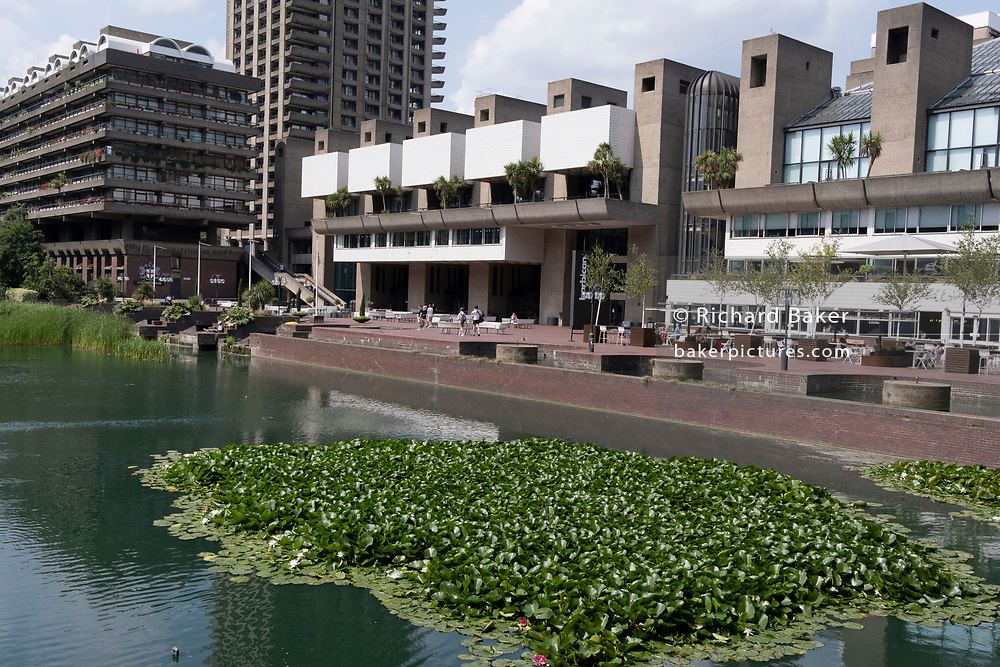 An exterior summer landscape of the Barbican, on 21st July 2021, in London, England. The Barbican Centre is a performing arts centre in the Barbican Estate of the City of London but whose area was formerly known as Cripplegate - destroyed on the evening of 29 December 1940, when tens of thousands of bombs and incendiaries were dropped on the City by the German Luftwaffe in WW2.