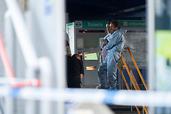© Licensed to London News Pictures. 10/07/2020. London, UK. A Forensics Officer  talks to colleagues at a crime scene at Crossharbour DLR station in Poplar. Police were called shortly after 18:00hrs to reports of two males injured at Alexia Square, E14 close to Crossharbour DLR station. Officers attended and found a man, believed aged in his late teens or early 20s, suffering stab injuries. Emergency services provided first aid but despite their efforts, he was pronounced dead at the scene. A second male, believed aged in his late teens, was taken by the LAS to an east London hospital. Photo credit: George Cracknell Wright/LNP