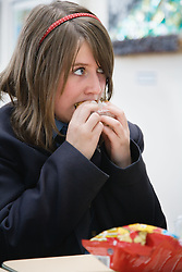 Secondary school student eating sandwich from packed lunch,