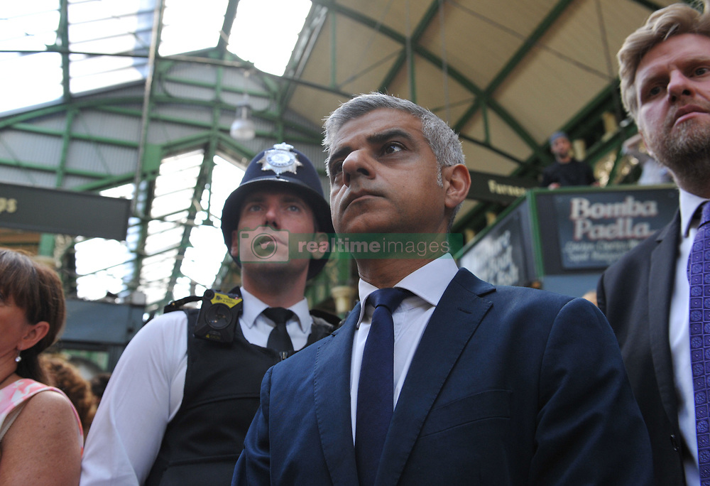 Mayor of London Sadiq Khan joins traders and visitors for a minute's silence to remember the victims of the London Bridge terror attack before the market bell is rung to mark the opening of Borough Market.
