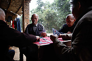 76 year old Yang Caiguan plays cards with friends near his residence in Daoxian, Hunan Province, China, on Friday, 15 October 2010. Yang, a farmer and rural laborer for most of his life, moved into a newly built apartment that was bought and furnished by his youngest son last year, one of many that has done so in China's continued drive to urbanize its vast rural population.