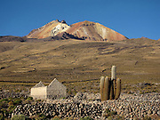A small town sits at the foot of the Volcan Thunupa volcano; the hillsides are covered with walls delineating the quinoa farms. Volcan Thunupa sits at the north edge of the Salar de Uyuni, the world's largest salt flat, in the Bolivian Altiplano