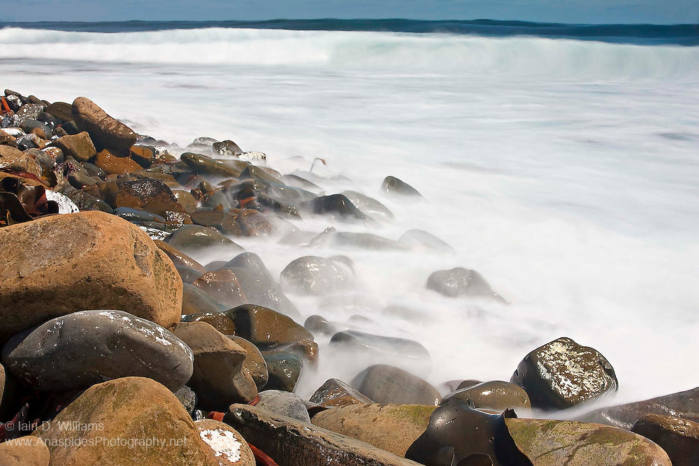 Waves pound the shoreline of a remote boulder beach in the Falkland Islands
