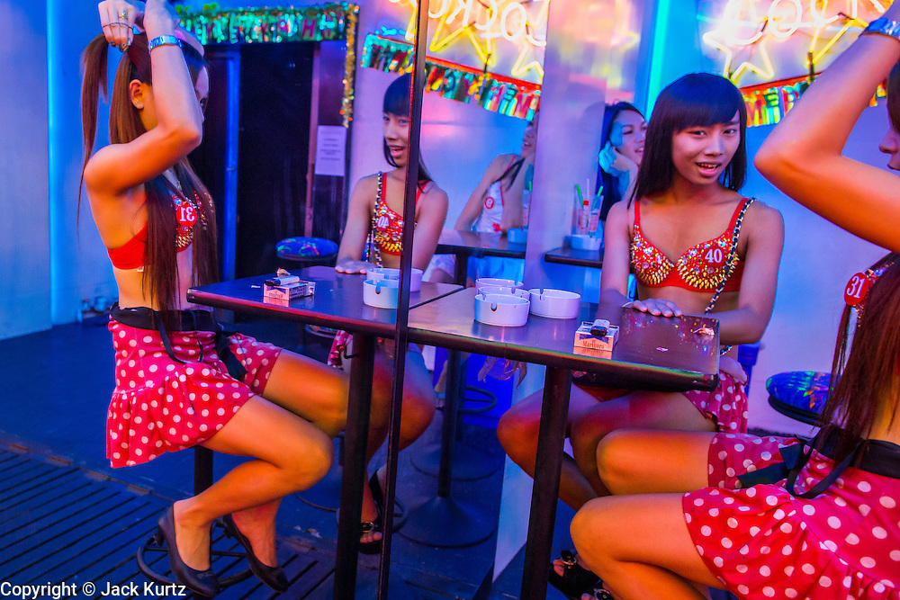 """12 JANUARY 2013 - BANGKOK, THAILAND:  Ladyboy entertainers check themselves in the mirror in front of the Cockatoo bar in the Soi Cowboy red light district in Bangkok. In Thai, the ladyboys are called kathoey. Many work in the entertainment and night life sectors of the Thai economy. Prostitution in Thailand is illegal, although in practice it is tolerated and partly regulated. Prostitution is practiced openly throughout the country. The number of prostitutes is difficult to determine, estimates vary widely. Since the Vietnam War, Thailand has gained international notoriety among travelers from many countries as a sex tourism destination. One estimate published in 2003 placed the trade at US$ 4.3 billion per year or about three percent of the Thai economy. It has been suggested that at least 10% of tourist dollars may be spent on the sex trade. According to a 2001 report by the World Health Organisation: """"There are between 150,000 and 200,000 sex workers (in Thailand).""""    PHOTO BY JACK KURTZ"""