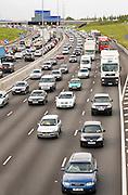 Four-lane traffic cars and trucks motoring in congestion on M25 motorway, London, United Kingdom