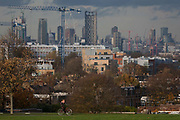 With the capital rising in the background, a cyclist rides through Brockwell Park, on 18th November 2016, in Herne Hill, Lambeth SE24 south London, England.