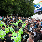 Police lines outside the Cuadrilla drill site main gate stop the march from getting any further. Thousands turned out for a march of solidarity against fracking in Balcombe. The village Balcombe in Sussex is the  centre of fracking by the company Cuadrilla. The march saw anti-fracking movements from the Lancashire and the North, Wales and other communities around the UK under threat of gas and oil exploration by fracking.