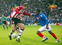 Photo: Scott Heavey.<br /> Portsmouth v Southampton. FA Barclaycard Premeirship. 21/03/2004.<br /> Yakubu (R) of Portsmouth has his shirt tugged by Claus Lundekvaum