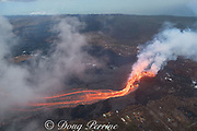 Aerial view of Kilauea Volcano east rift zone erupting hot lava from Fissure 8 in Leilani Estates subdivision near the town of Pahoa. The lava drains downhill as an incandescent river toward Kapoho, Puna District, Hawaii Island ( the Big Island ), Hawaiian Islands, U.S.A.; the steam cloud in the background at left is the ocean entry of the lava river