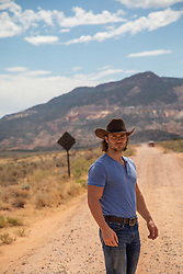 sexy cowboy with long hair on a dirt road with mountain views
