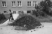 Duitsland, Weimar, 1-7-1990 Op deze dag werd de duitse monetaire eenwording effectief. De burgers van de ddr konden hun marken inwisselen tegen de west-duitse mark, in winkels had een grote operatie plaatsgevonden om prijzen aan te passen. Een berg bruinkool blokken wordt een kelder in gedragen. umtausch,mauerfall,monetaire,eenwording,monetair,samengaan,eenwording,duitse,hereniging,herenigen,bruinkool,vervuiling,milieu,mileuvervuiling,brandstof,vervuilende,industrie,zware,luchtvervuiling,centrale,elektriciteitscentrale,electriciteitscentrale,vies,landschap,bruinkolen,dagbouw,bruinkoolwinning,mijnbouw,economie Foto: Flip Franssen/Hollandse Hoogte