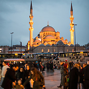 Crowds gather in a plaza on the waterfront in the Eminonu quarter of Istanbul. In the background is the New Mosque (Yeni Cami).