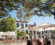 People sitting outside cafes historic square Placeta de San Miguel Bajo in the Albaicin district, Granada, Spain