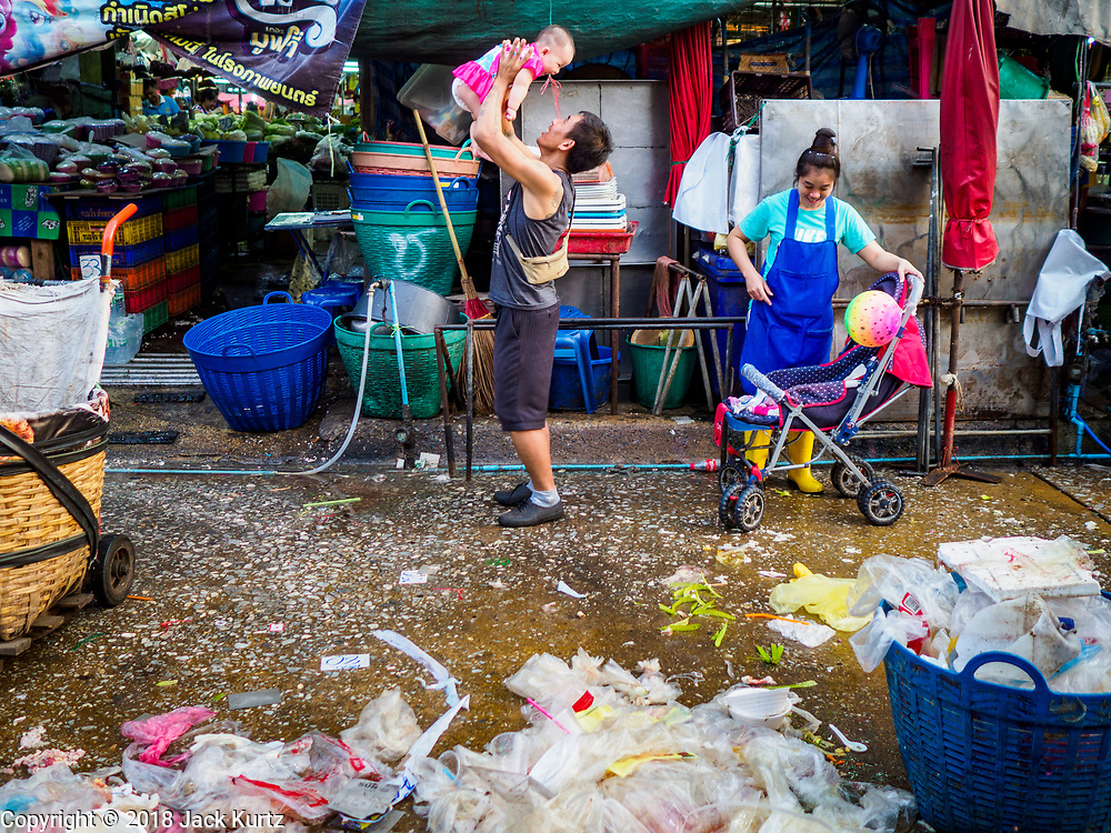 """04 DECEMBER 2018 - BANGKOK, THAILAND:  A man plays with his baby in front of a pile of plastic waste in Khlong Toei market. The issue of plastic waste became a public one in early June when a whale in Thai waters died after ingesting 18 pounds of plastic. In a recent report, Ocean Conservancy claimed that Thailand, China, Indonesia, the Philippines, and Vietnam were responsible for as much as 60 percent of the plastic waste in the world's oceans. Khlong Toey (also called Khlong Toei) Market is one of the largest """"wet markets"""" in Thailand. December 4 was supposed to be a plastic free day in Bangkok but many market venders continued to use plastic.     PHOTO BY JACK KURTZ"""