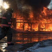 A volunteer firefighter walks past a burning building during  a practice burn on Main street in Rockerville on Saturday morning.