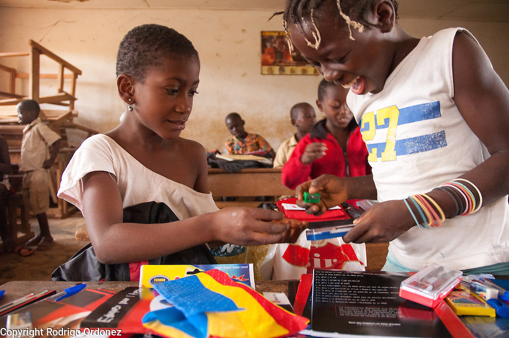 Dorée (left), 9, and Carole, 11, smile while examining the contents of the backpacks with school materials they just received. <br /> Save the Children distributed education kits to students at Groupe Scolaire Quartier Lycée in Man, western Côte d'Ivoire. Children received a backpack with school supplies such as pens, pencils, sharpeners, notebooks, rulers, a pair of compasses and a portable chalkboard.