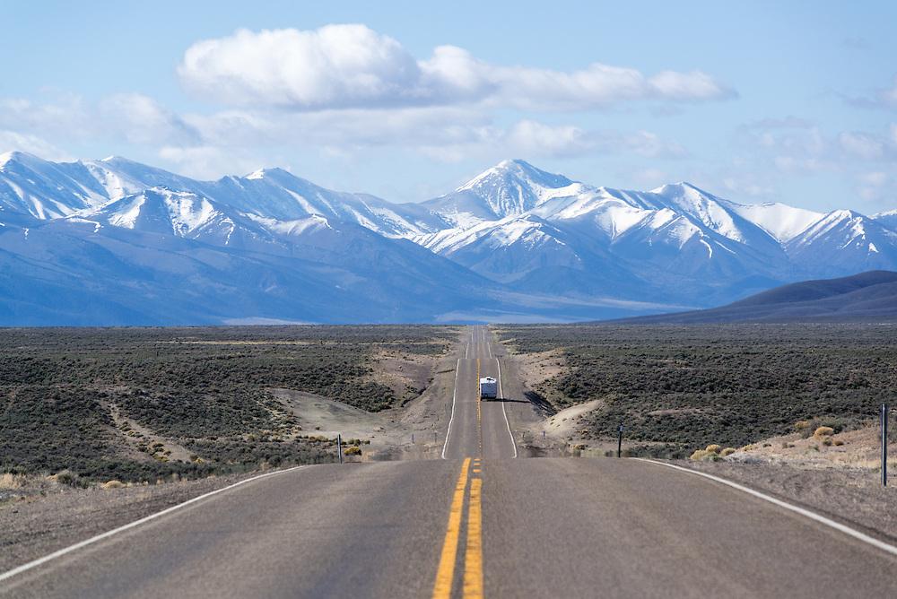 Camper trailer on a desert highway below the Toiyabe Range, Nevada.
