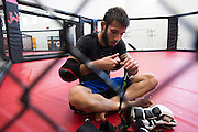 UFC flyweight Matheus Nicolau of Brazil takes off his hand wraps after sparing with Holly Holm at Jackson Wink MMA in Albuquerque, New Mexico on June 9, 2016.
