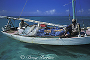 Carib fishermen in traditional sailing smack with fish drying on tarp during grouper spawning season, near Caye Glory, inside Belize Barrier Reef, Belize, Central America ( Caribbean Sea )