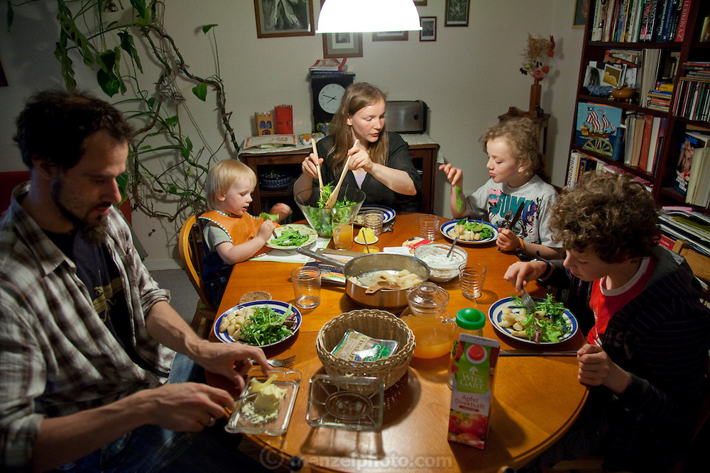 Hollmann Sturm family in Hamburg, Germany photographed for the Hungry Planet: What I Eat project with a week's worth of food. At supper, Astrid Hollmann, 38, and Michael Strum, 38, and their three children Lenard, 12, Malte Erik, 10, and Lillith, 2.5 Model Released.